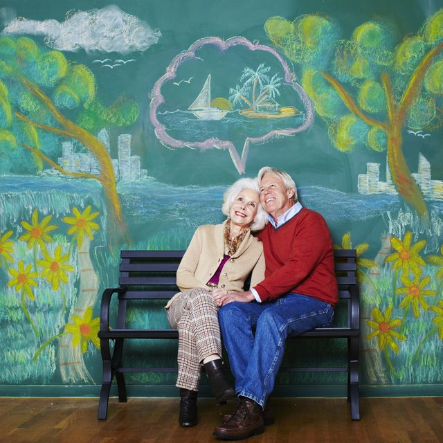 an elderly couple daydreaming on a park bench