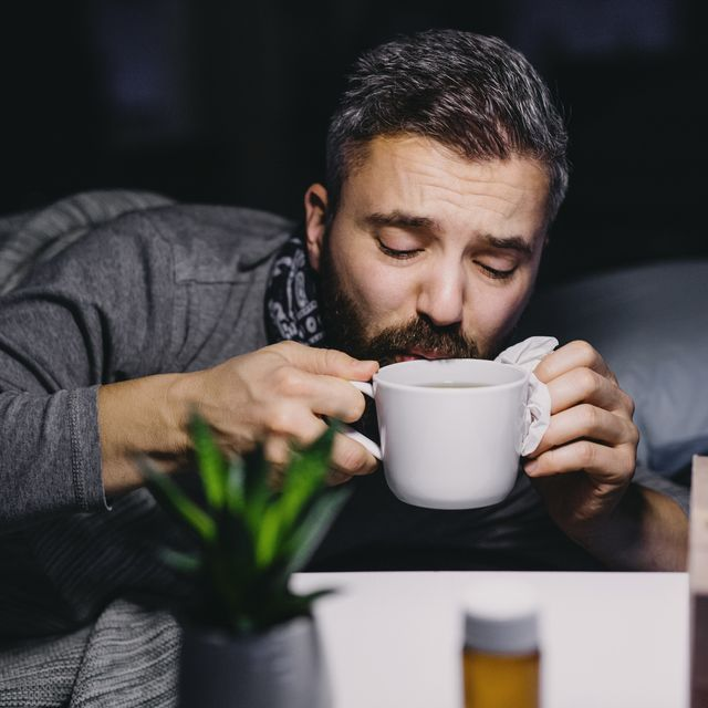 an ill mature man patient in bed at home, drinking hot tea