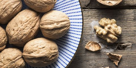 an overhead bowl of walnuts on a rough wooden background