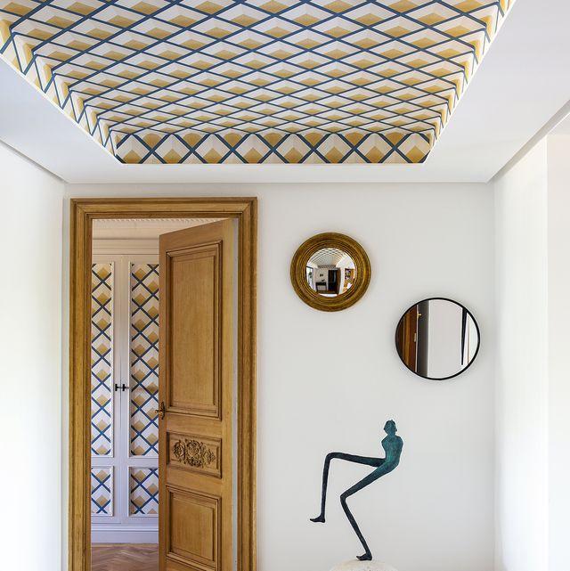 recibidor con espejos redondos y papel geométrico