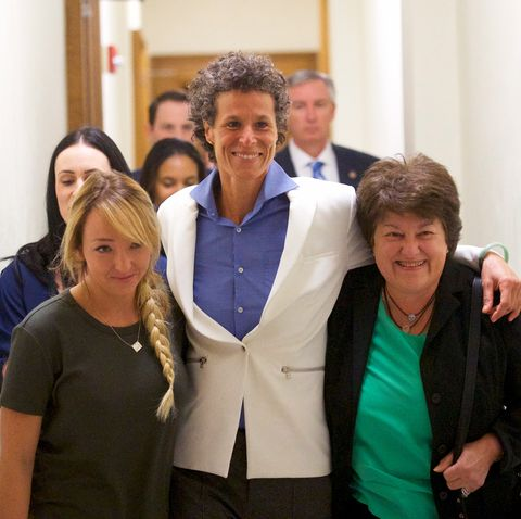 andrea constand with her lawyers wearing a white blazer and blue top walking through court