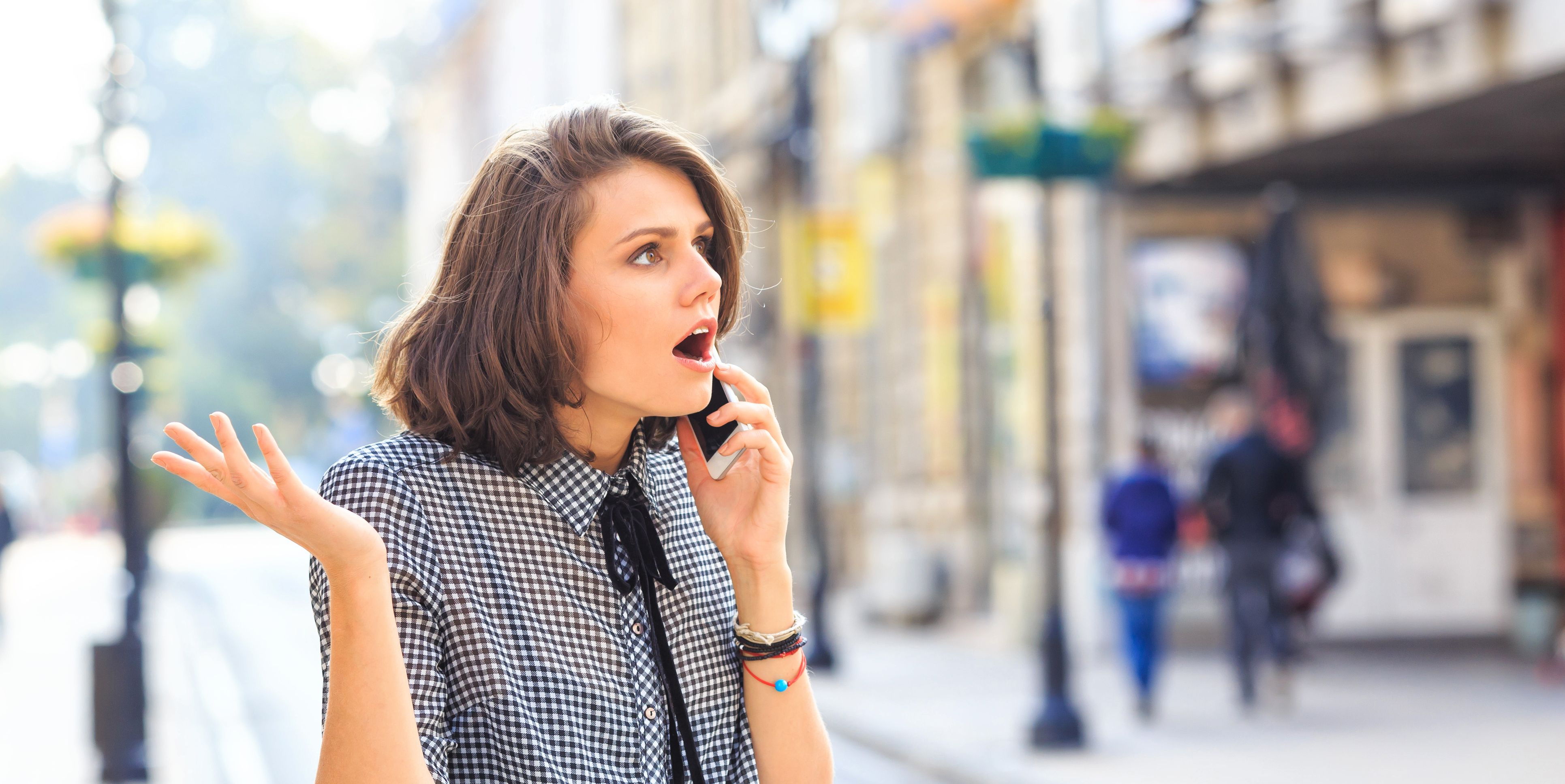 Angry woman talking on smart phone on street