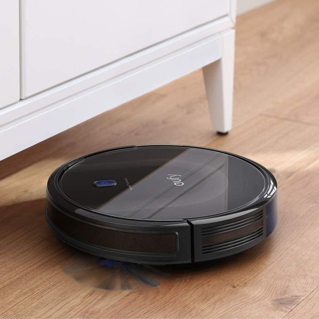 eufy by anker boostiq robovac on wood floor under cabinet