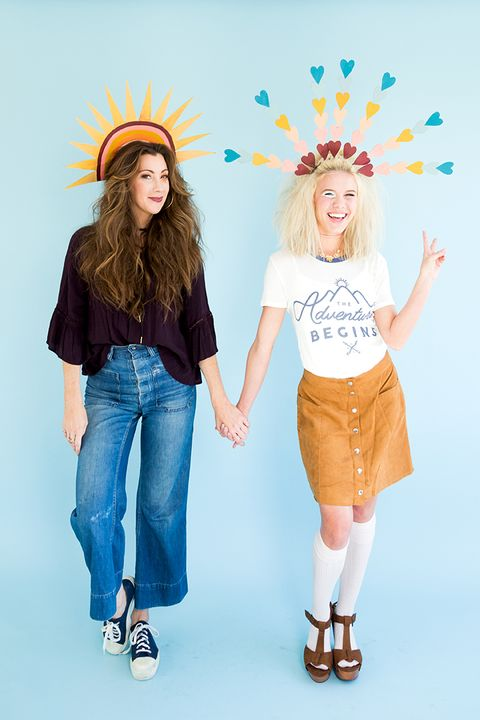 one woman dress in jeans with a sun headpiece, other woman dressed in skirt and knee socks with a hearts headpiece, giving the peace sign
