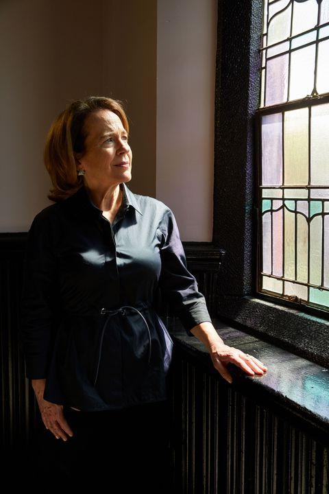 anne barrett doyle wearing a black blouse standing near a stained glass window with light shining on her face, highlighting her shoulder length auburn hair and green eyes