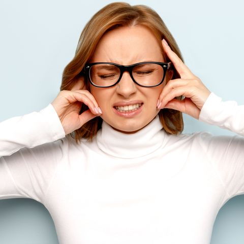 annoyed business woman in glasses shuts ears, close eyes, trying keep calm and take control over emotions, unwilling hear