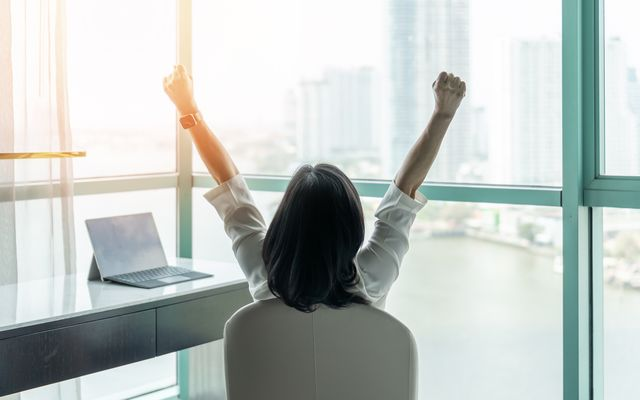 woman sitting in an office in an excited pose