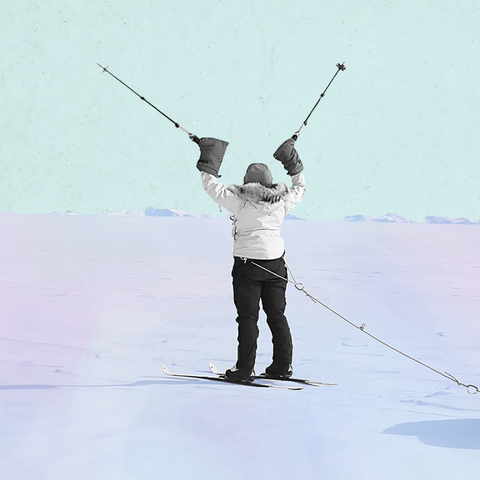 a woman standing in antarctic snow with two ski poles in her hands raised over her head in triumph