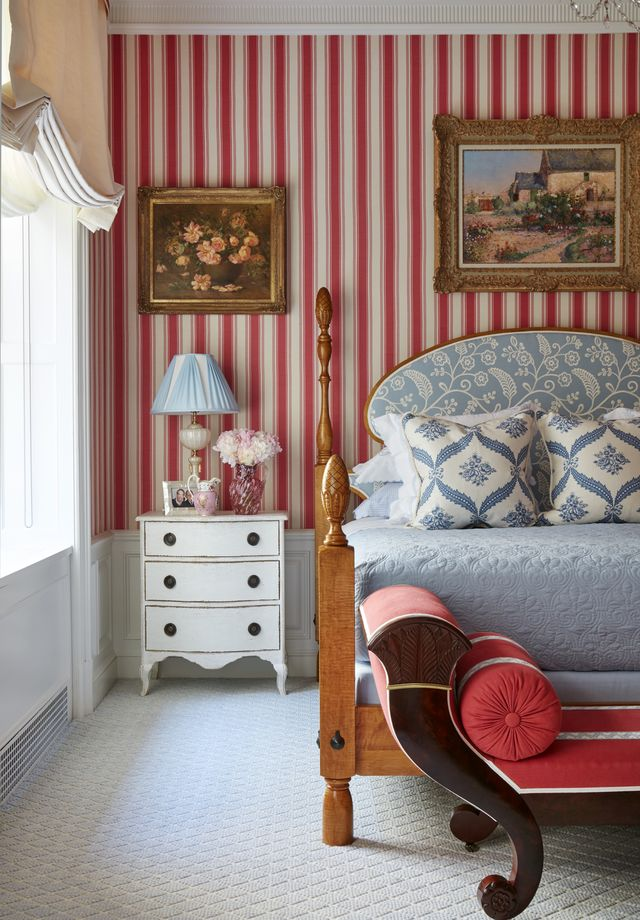 a luxe bedroom with red and white striped walls and blue and white bedding