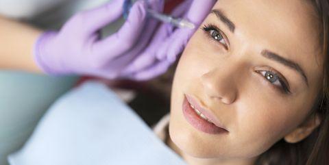 vrouw krijgt filler botox toegediend