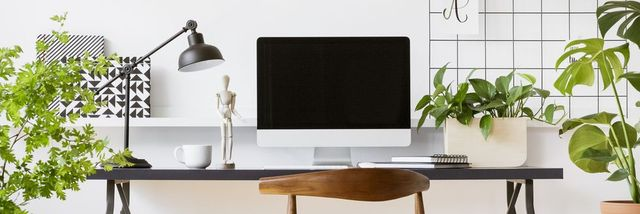 antique wooden chair by a desk with an empty, mock up computer screen in a stylish home office interior for a freelancer
