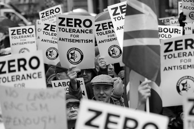 antisemitism hot   people hold up placards and union flags as they gather for a demonstration organised by the campaign against anti semitism outside the head office of the british opposition labour party in central london on april 8, 2018   labour leader jeremy corbyn has been under increasing pressure to address multiple allegations of anti semitism within the party, which saw protesters gather outside the party's head office in london after jewish campaigners demonstrated outside parliament two weeks ago photo by tolga akmen  afp        photo credit should read tolga akmenafp via getty images