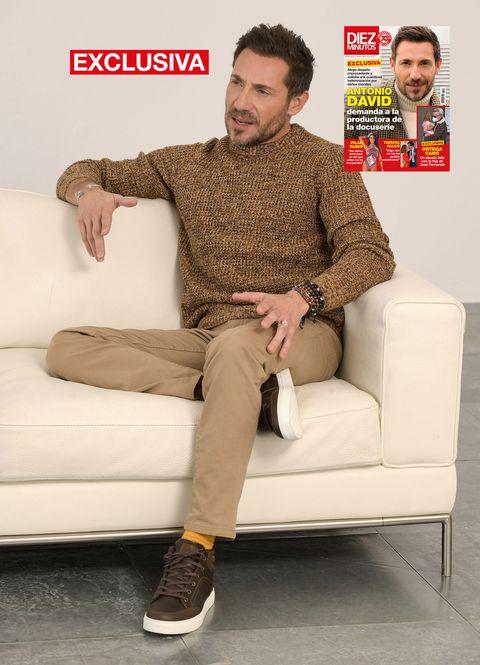 el ex de rocío carrasco posa con un jersey de color marróin y pantalones a juego