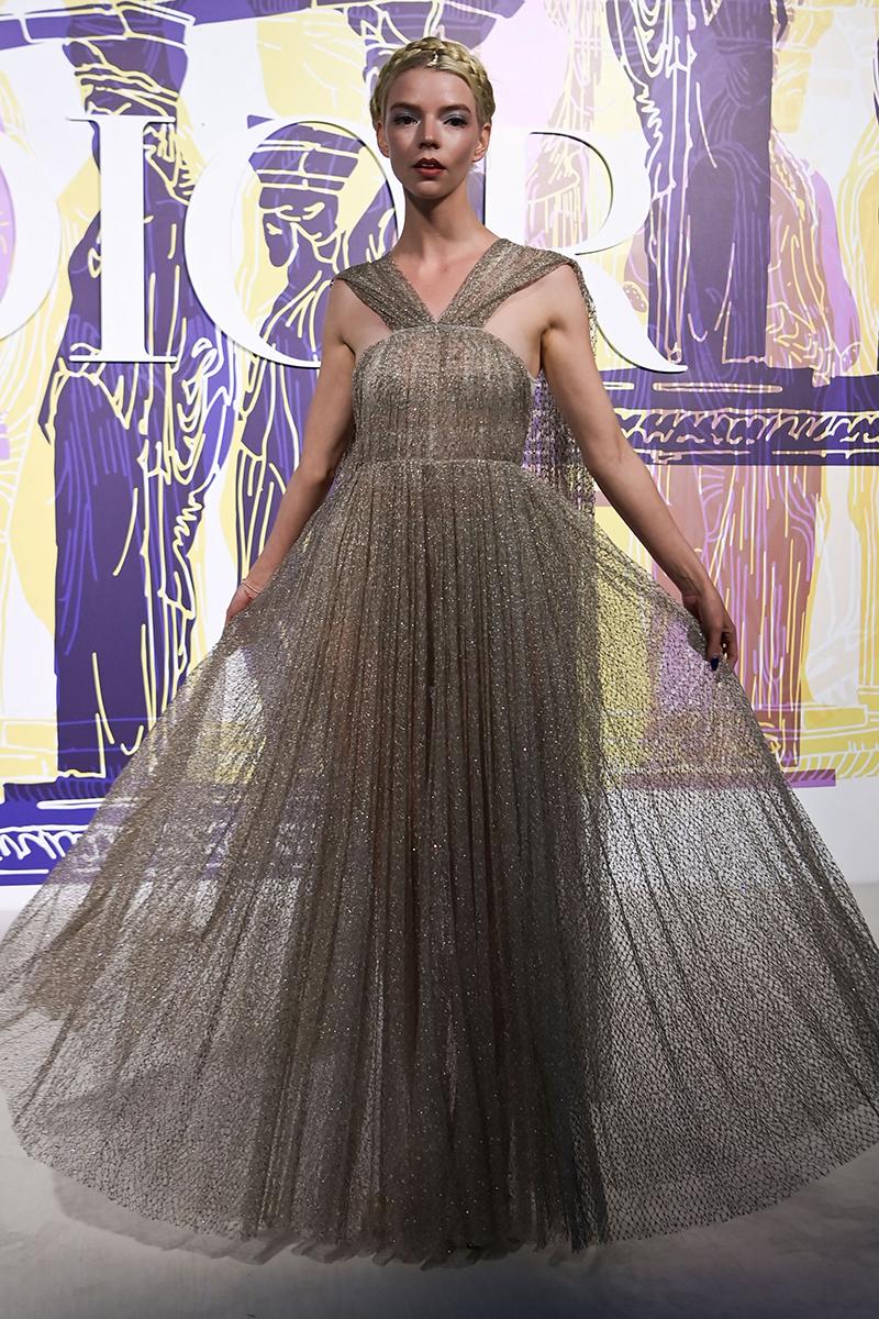 Anya Taylor-Joy helps Cara Delevingne fix a wardrobe malfunction at the Dior show