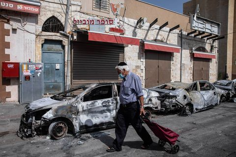 man walking in front of a burnt out car