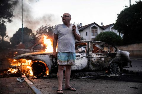 man in flip flops in front of a burning car
