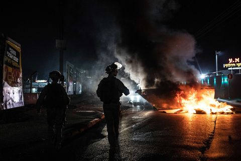 Police in riot gear stand near burning car at night