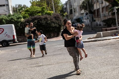 Woman running with her children in the streets of Ashdod