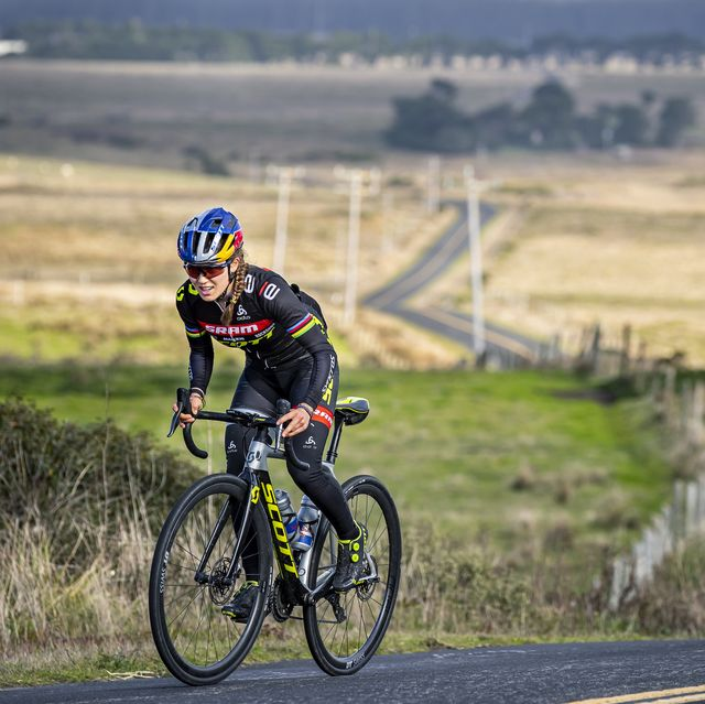 Kate Courtney rides a road bike uphill