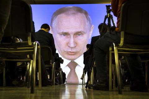 Journalists watch as Russian President Vladimir Putin gives his annual state of the nation address in Manezh in Moscow, Russia, Thursday, March 1, 2018.