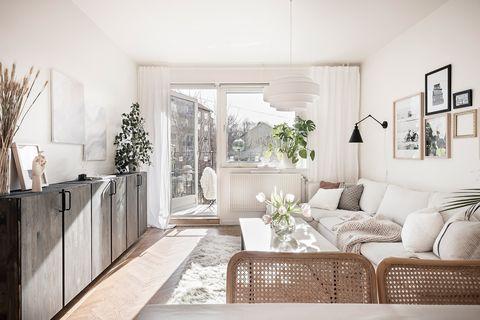 salón con terraza de estilo nórdico decorado en blanco
