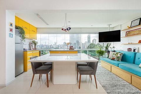 cocina moderna diseñada en amarillo con comedor y ventanales con vistas a la ciudad