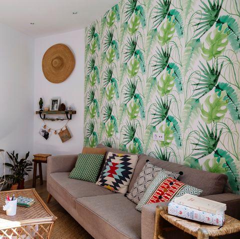 salón de estilo boho con sofá gris, papel pintado con motivos botánicos y muebles de fibras