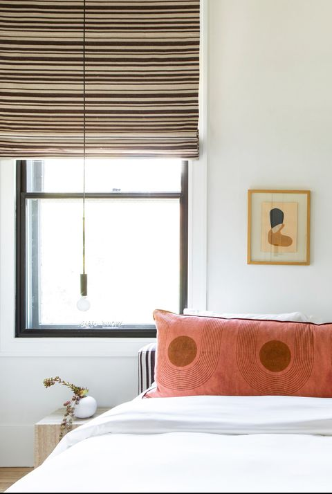 bedroom with orange pillow and window