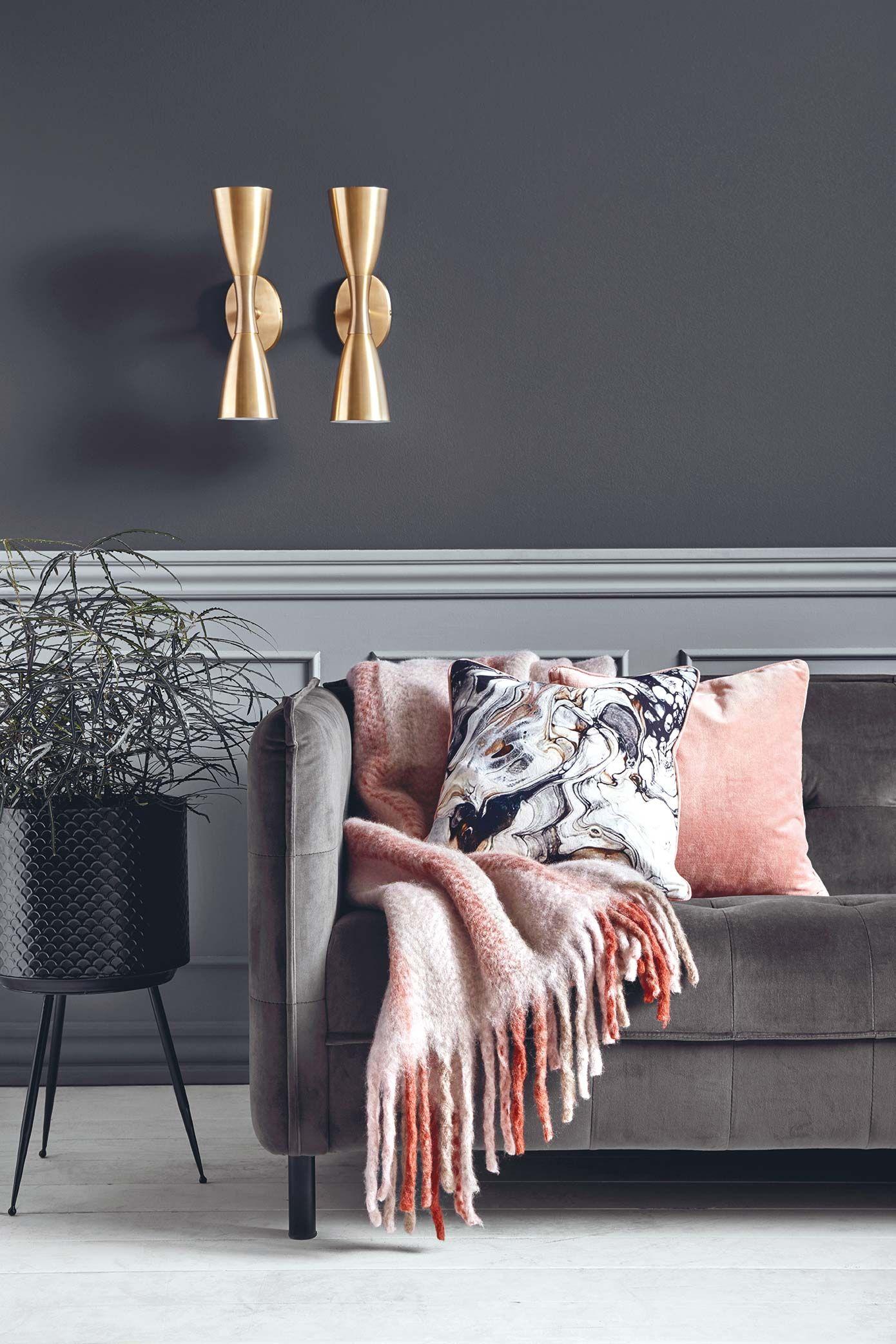 Sofá gris con manta y cojines en rosa