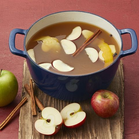 mulled apple cider in blue pot with apples and cinnamon sticks
