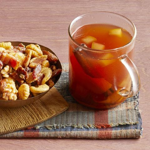 mulled cider with bourbon in glass mug with nuts on the side