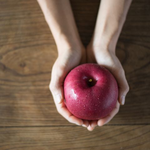 Apple in hands on a wooden table