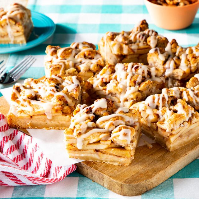 apple pie bars with walnuts on wooden board with parchment paper and red striped tea towel