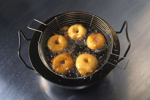 Apple rings coated in batter deep-frying in pan