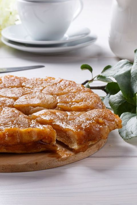 Apple Tarte Tatin - classic French upside-down tart. Whole fruit pie on white table. Rustic style.
