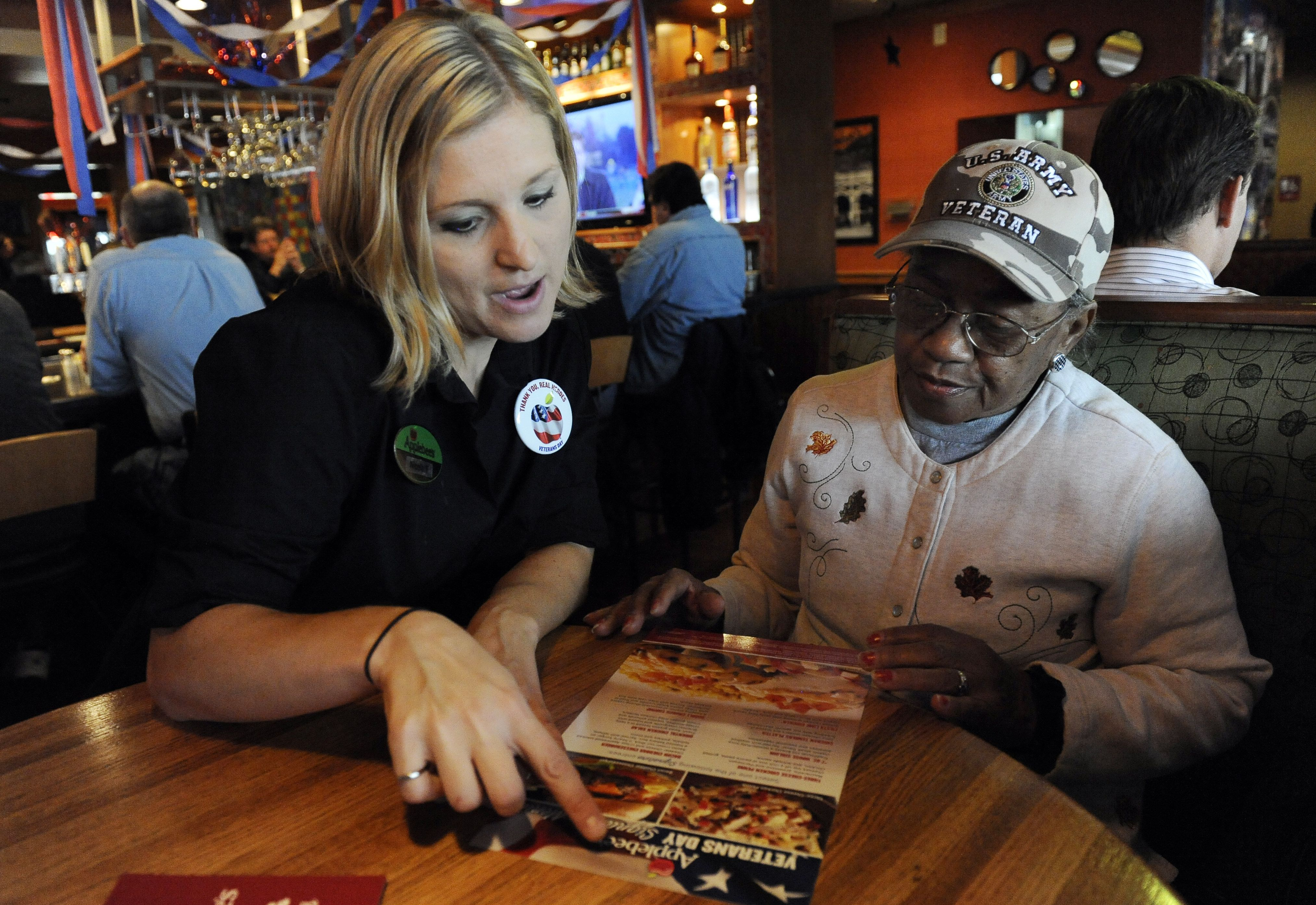 GLENDALE, CO--NOVEMBER 11TH 2010-- Applebee's restaurant waitress, Nicole Thomason, left, points out the menu to U.S. Army Veteran Nurse, Dolores Collins, for a free lunch at Applebee's restaurant at 410 S. Colorado Blvd Thursday, Veterans Day, November 1
