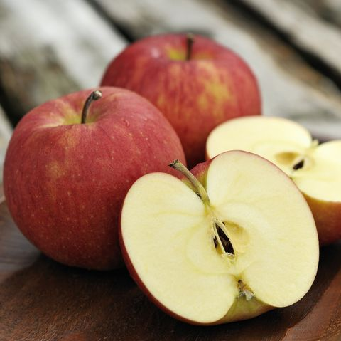 Apples piled on a wooden tray outdoors