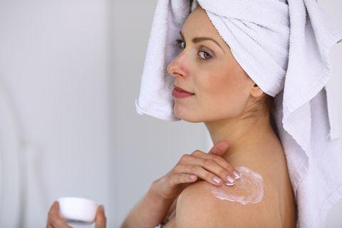 mujer, con toalla en la cabeza, se pone crema en el hombro