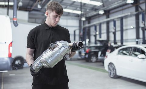 apprentice holding catalytic converter in car service centre