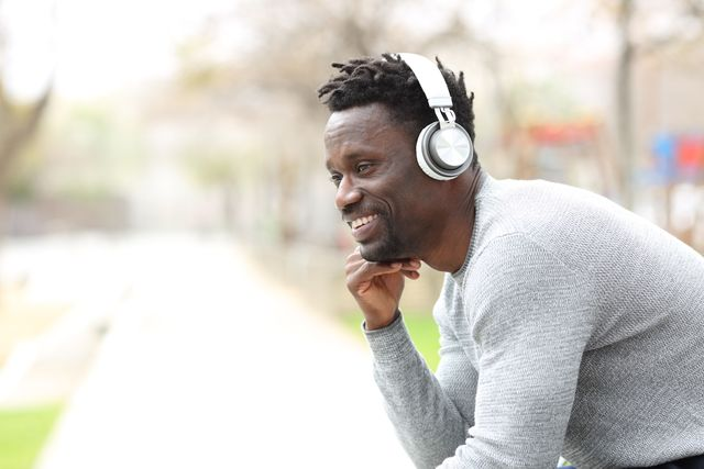 happy black man listening to music with headphones sitting in the park