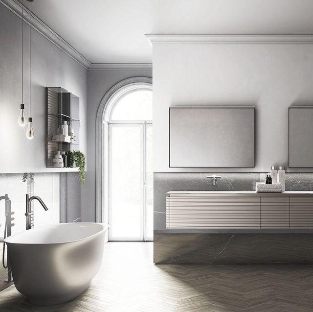 Grey and white bathroom with freestanding bath, twin sink vanity and herringbone floor