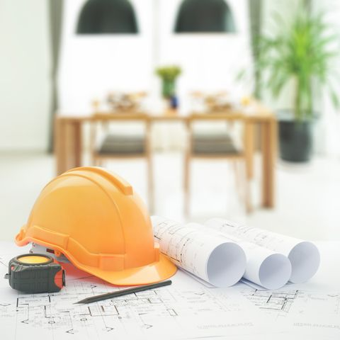 architectural blueprint with safety helmet and tools over dining table and comfortable chairs in modern home