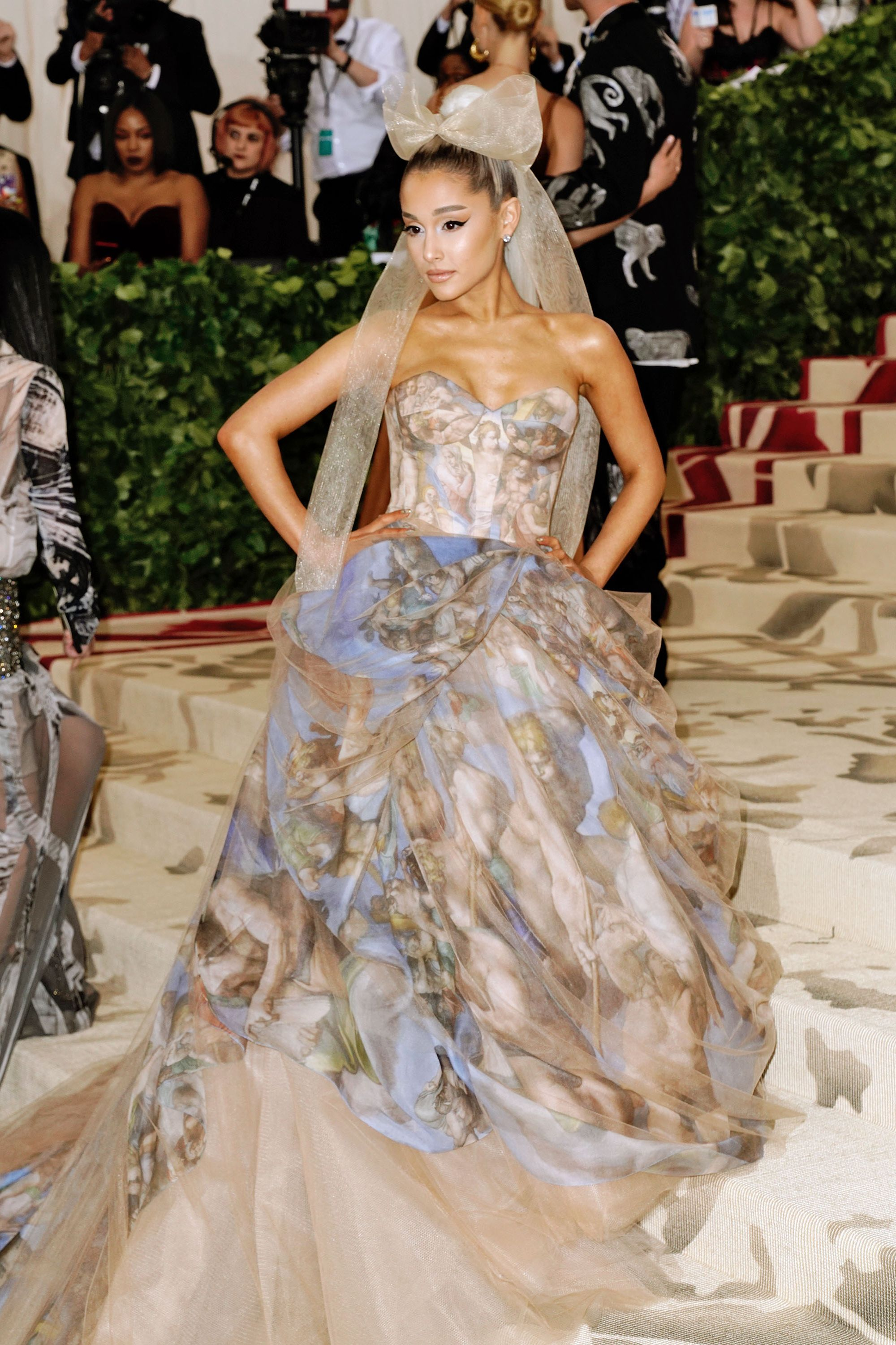 """Ariana Grande Grande made her Met Gala debut last year, playing into the """"Heavenly Bodies,"""" theme by donning a gorgeous Vera Wang gown influenced by Michelangelo's The Last Judgment. The singer is scheduled to perform tonight at the Staples Center in downtown Los Angeles for her Sweetener tour, and can't make this year's Gala."""
