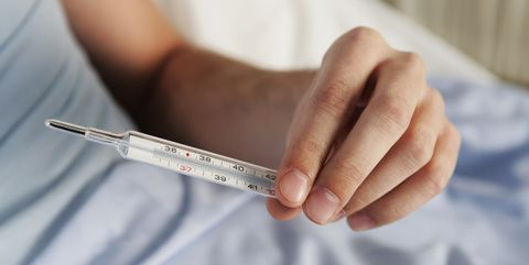 A patient checking a thermometer