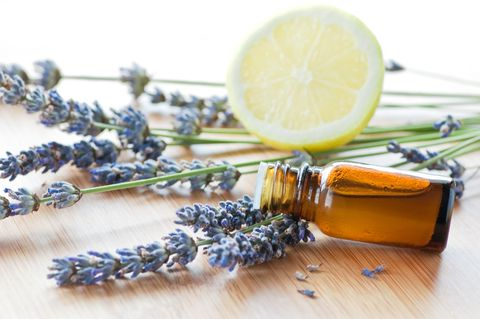 aromatherapy herbs, oil, and lemon on wood