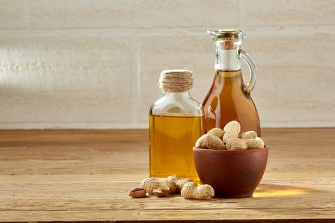 Aromatic oil in a glass jar and bottle with peanuts in bowl on wooden table, close-up.