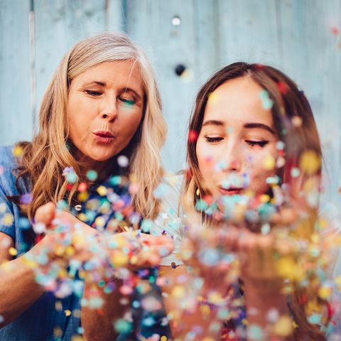 Mother blowing confetti out of her hands with her daughter