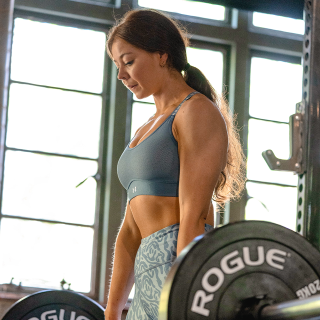 a woman in gym clothes working out in a gym