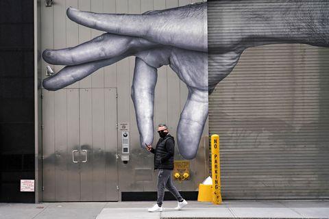 Un hombre camina por las calles de Nueva York durante el confinamiento. Su silueta se enmarca en un dibujo en una pared de una gran mano que parece que le levanta en vilo.