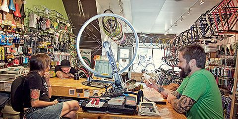 Table, Bicycle tire, Artist, Stool, Shelf, Artisan, Bicycle wheel rim, Desk, Machine, Bicycle wheel,
